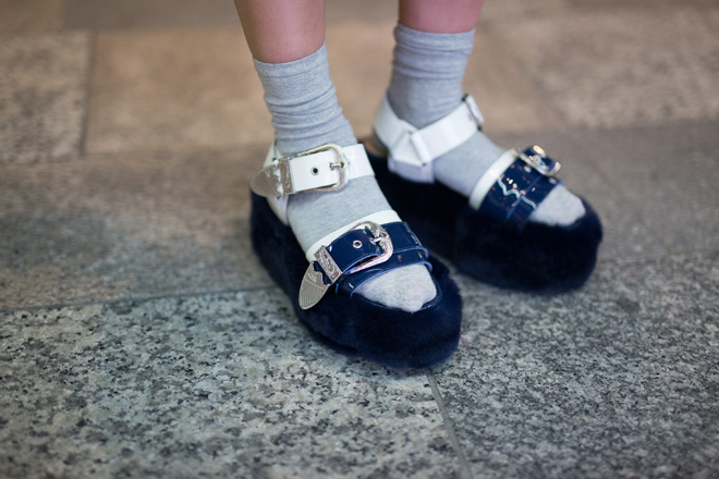 Серые носки сочетаются с сине-белыми сандалиями на высокой меховой подошве и с ремешками.