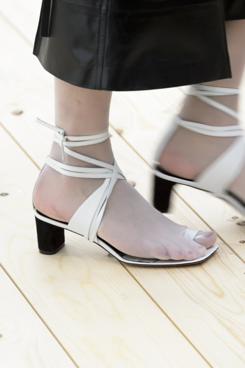 Белые полупрозрачные носки с белыми кожаными сандалиями  с переплетами на невысоком каблуке.