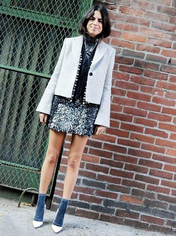 На девушке коктейльное платье в пайетках, серый пиджак, синие носки и белые туфли.