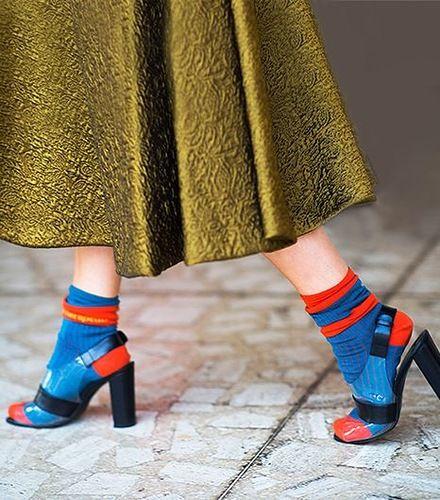 Яркие сине-оранжевые носки в сочетании с такого же цвета сандалиями на каблуке.