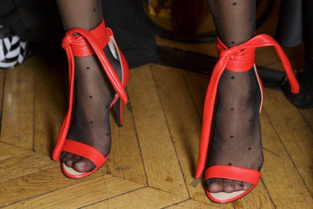 Черные полупрозрачные носки в сочетании с ярко-оранжевыми кожаными босоножками на каблуке.