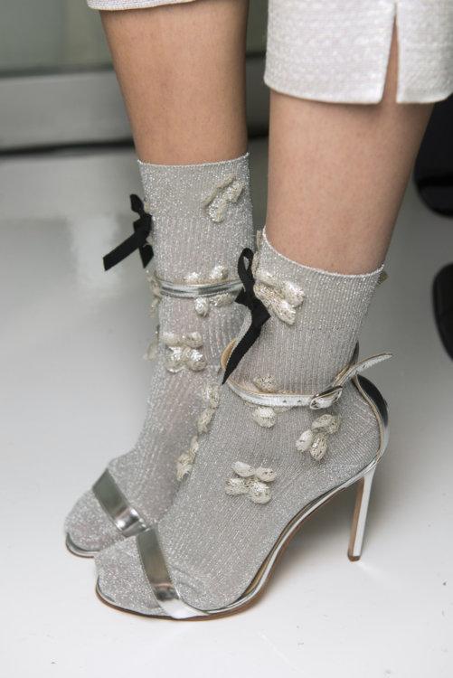 Босоножки на шпильке цвета металлик в сочетании с серыми носками с декором из люрекса.