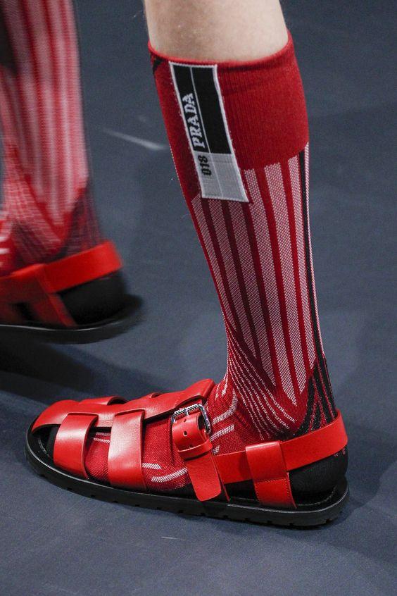 Сочетание красных кожаных мужских сандалий с бордовыми гольфами на показе Prada.