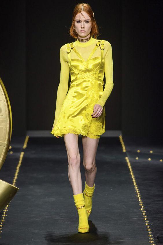 Желтое короткое шелковое платье, такого же цвета босоножки и длинные носки.