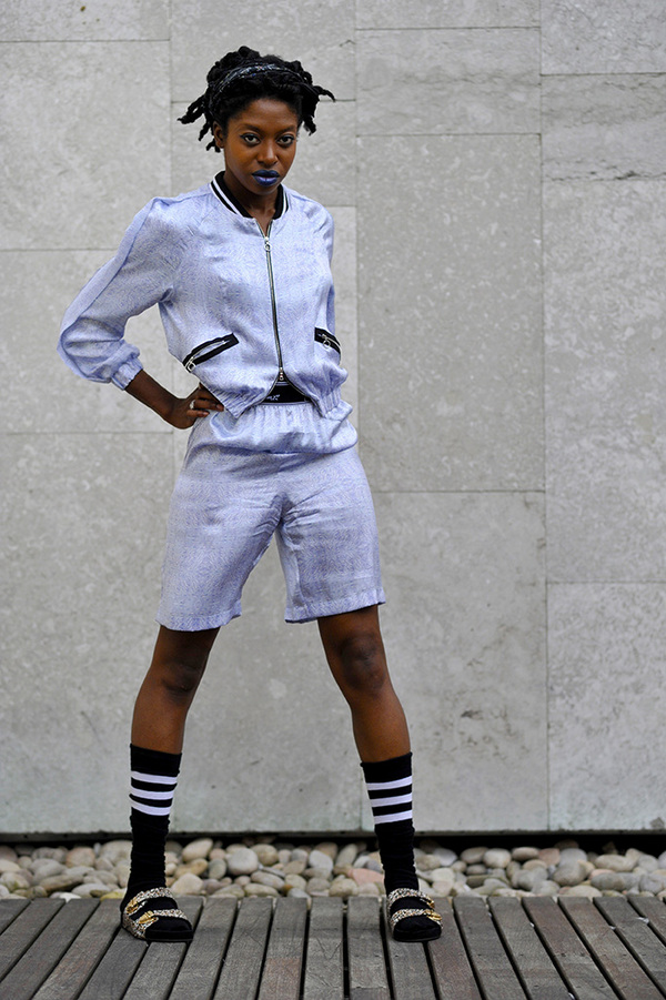 На девушке спортивный небесно-голубой костюм, черные высокие гольфы с тремя белыми полосами и леопардовые сандалии с ремешками.