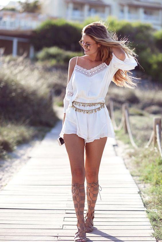 На девушке белый ромпер с поясом и бежевые гладиаторы на шнуровке.