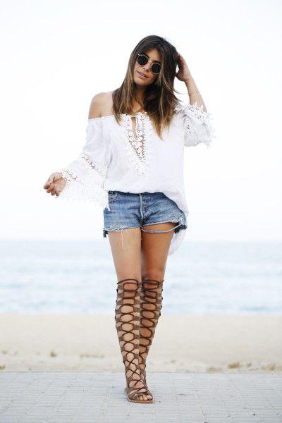 Белая свободная рубашка со спущенными плечами и ажурными вставками, джинсовые шорты и коричневые гладиаторы по колена со шнуровкой.