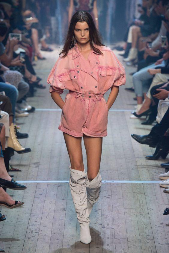 На девушке свободный нежно-розовый комбинезон с карманами, заклепками и шнуровкой на талии и белые высокие широкие сапоги с заклепками.