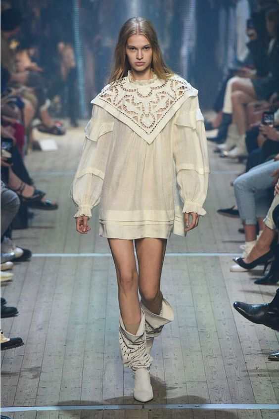 На девушке короткое белое платье прямого кроя с объемными рукавами и треугольным воротником, белые кожаные сапоги с дырками и свободным верхом.
