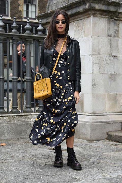 Девушка надела цветочное черное платье свободного кроя длины миди, черные кожаные сапоги в стиле милитари, кожаную куртку, поясную сумку горохового цвета и круглые черные очки.