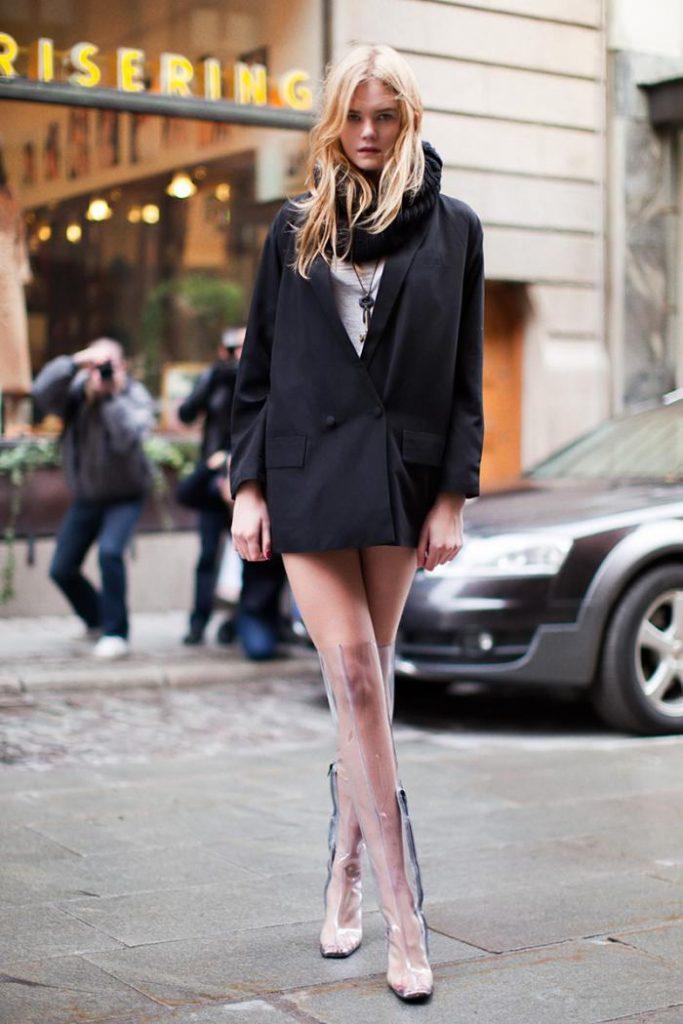 Девушка выбрала пластиковые ботфорты с квадратным носом, удлиненный черный пиджак и объемный шарф.