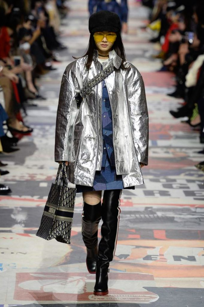 Прямая синяя короткая юбка, такой же длины плащ цвета металлик сочетается с кожаными черными ботфортами с лампасами. Образ дополнен сумкой, черным кепи и желтыми очками.