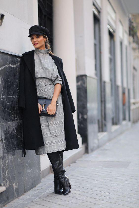 """Девушка выбрала серое платье-футляр в клетку с поясом длины миди, черное замшевое пальто прямого кроя ниже колена, черное кепи, кожаную сумку и ботфорты """"гармошкой"""" на широком каблуке с заостренным носом."""