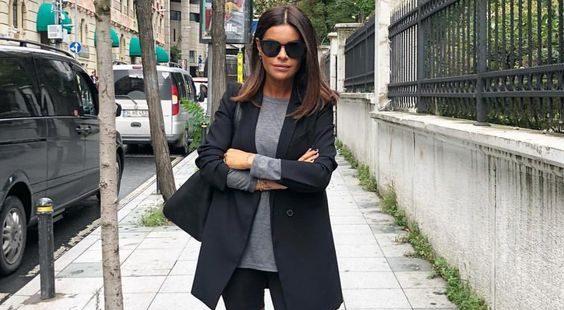 На девушке черные велосипедки, серый свободный гольф, черный удлиненный пиджак свободного кроя, очки, сумка и черные ботфорты на плоском ходу в ковбойском стиле.