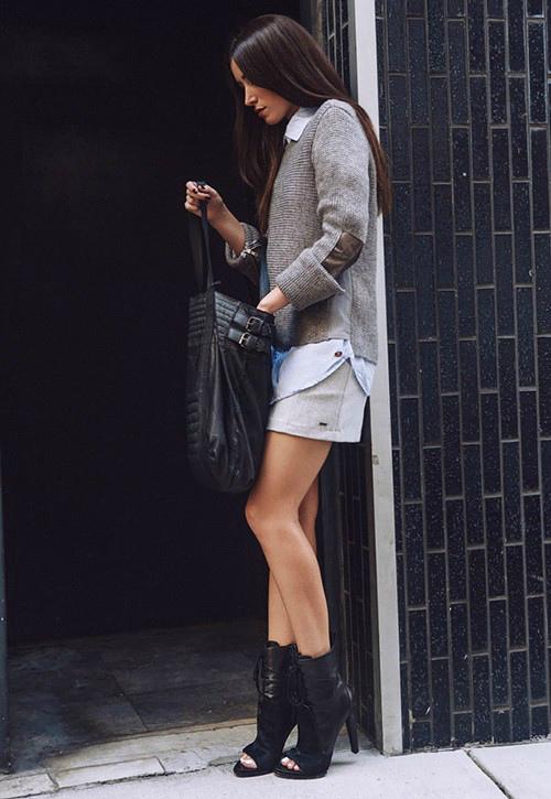 На девушке серый свитер-рубашка, светло-серая юбка-мини прямого кроя, черные сапоги на шнуровке и каблуке с открытым носом и черная большая сумка.