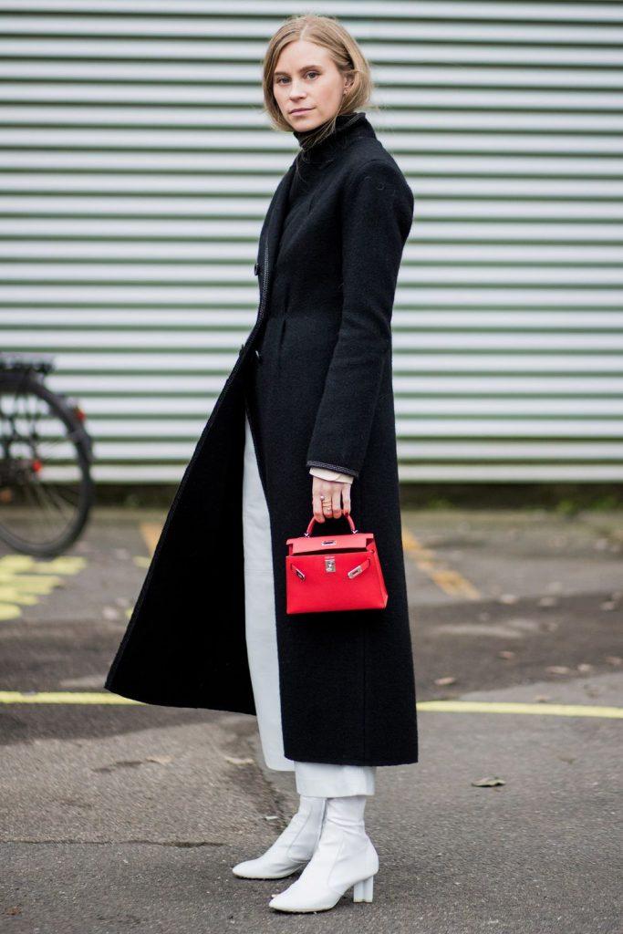 Девушка надела темно-серое пальто безупречного кроя длины миди, белые прямые джинсы длины 7/8, белые сапоги на небольшой толстом каблуке и выбрала маленькую красную сумку.