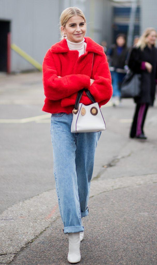 На девушке бежевый гольф, красная укороченная искусственная шуба с воротником, голубые джинсы мом, белые сапоги и такого же цвета сумка.