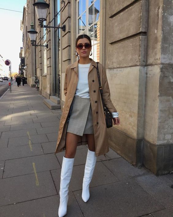 Девушка надела белую футболку, светло-серую юбку-мини на запах, бежевый свободный тренч, белые кожаные ботфорты, поясную сумку и очки.