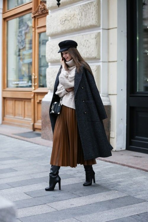 На девушке бежевый вязаный свитер oversize, коричневая юбка-плиссе длины миди,темно-серое пальто свободного кроя, кожаный ботфорты на каблуке с широким голенищем, сумка и кепи.