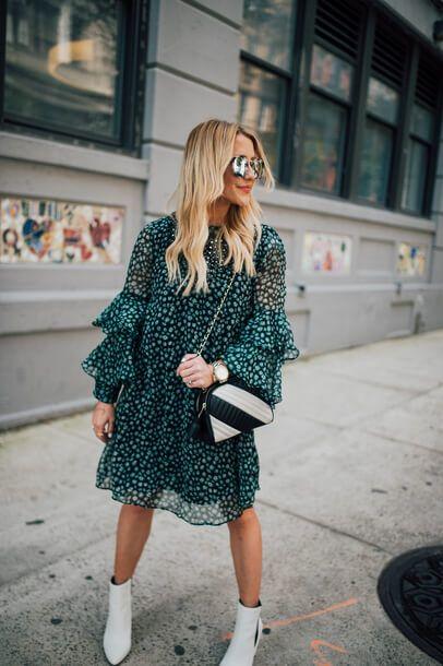 На девушке свободно платье с воланами изумрудного цвета с цветочным принтом, белые короткие сапоги на каблуке и поясная сумка треугольной формы.