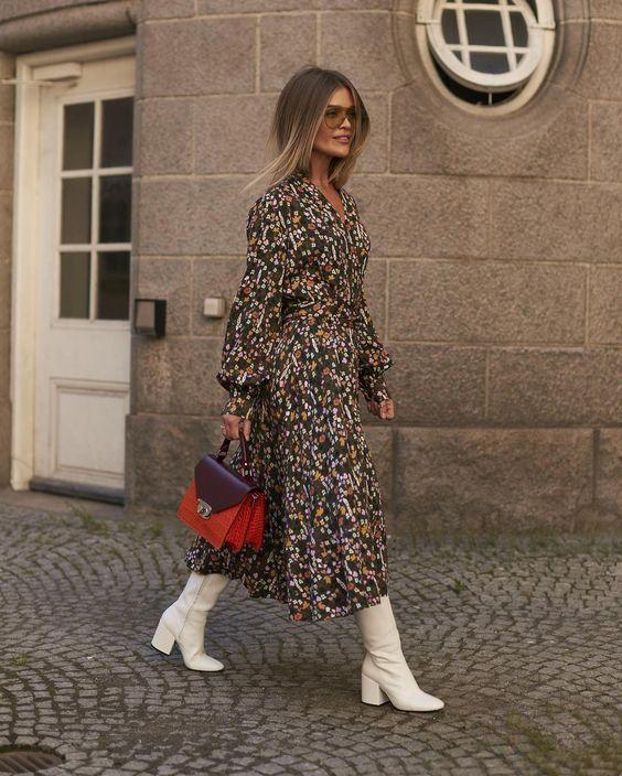Коричневое платье-миди с цветочным принтом в сочетании с белыми сапогами на невысоком широком каблуке, красной кожаной сумкой и очками.