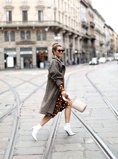 На девушке коричневое платье в белый горошек, клетчатое свободное пальто ниже колена, очки и белые ботильоны на шпильке.