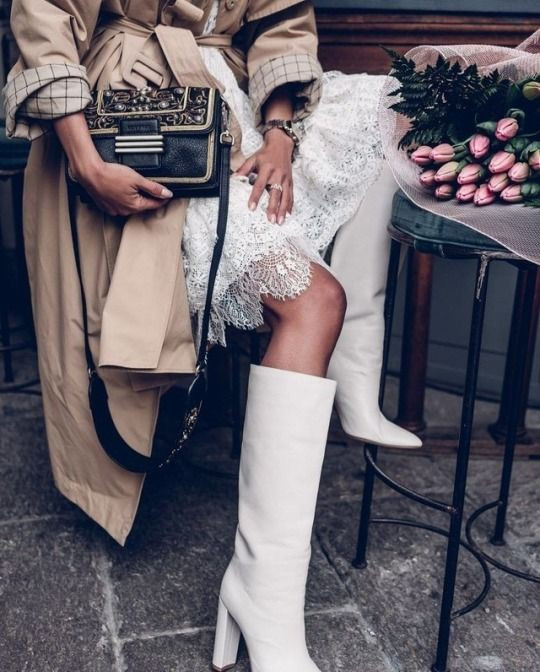 """На девушке нежное белое платье-мини с ажурными вставками, белые широкие сапоги-""""гармошкой"""" с высоким устойчивым каблуком, бежевый тренч с поясом и черная кожаная сумка с декоративными вставками."""