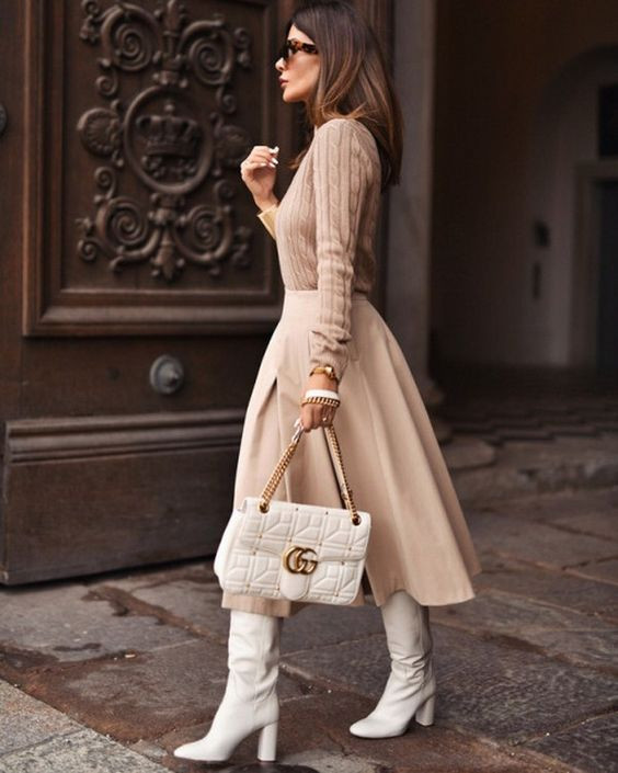 Бежевый свитер, на тон светлее пышная юбка-миди, белые сапоги с широким голенищем, округленным носом и устойчивым каблуком, белая кожаная сумка - стильный осенний лук.