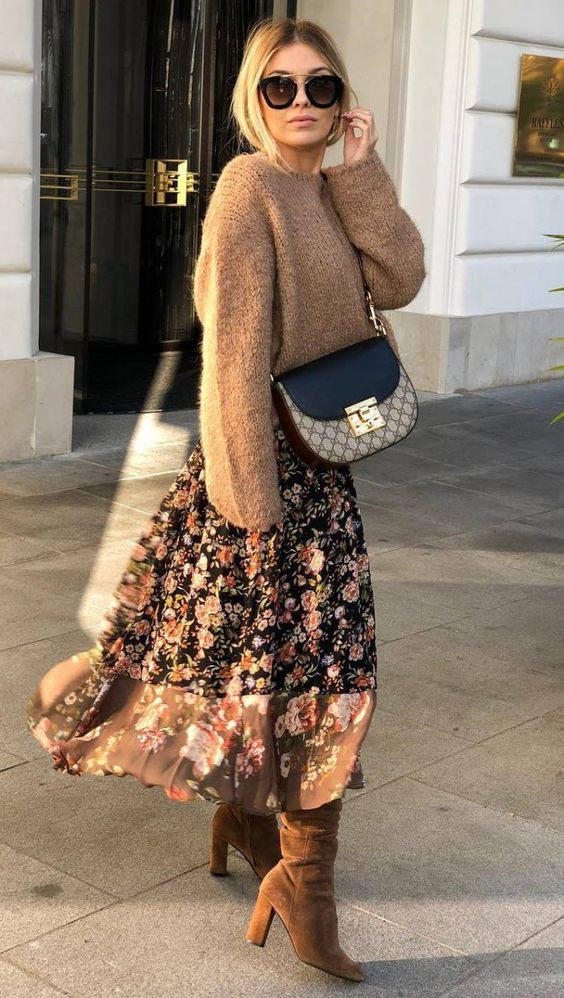 Девушка надела объемный светло-коричневый свитер, черную юбку-миди с воланами и цветочным принтом, замшевые коричневые сапоги с широким голенищем и  заостренным носом, поясную сумку.