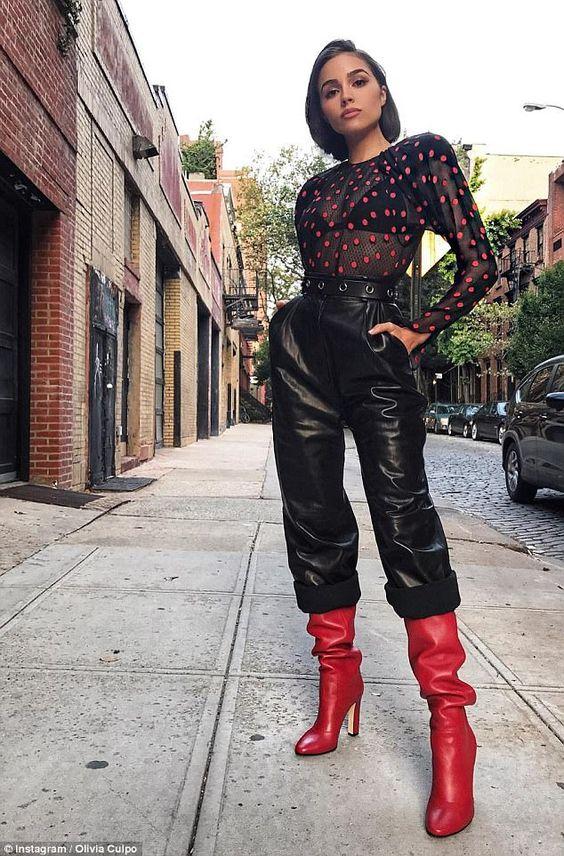 На девушке полупрозрачная черная рубашка в красный горох, кожаные черные брюки с завышенной талией и подкатами, яркие красные сапоги на высоком каблуке с широким голенищем.