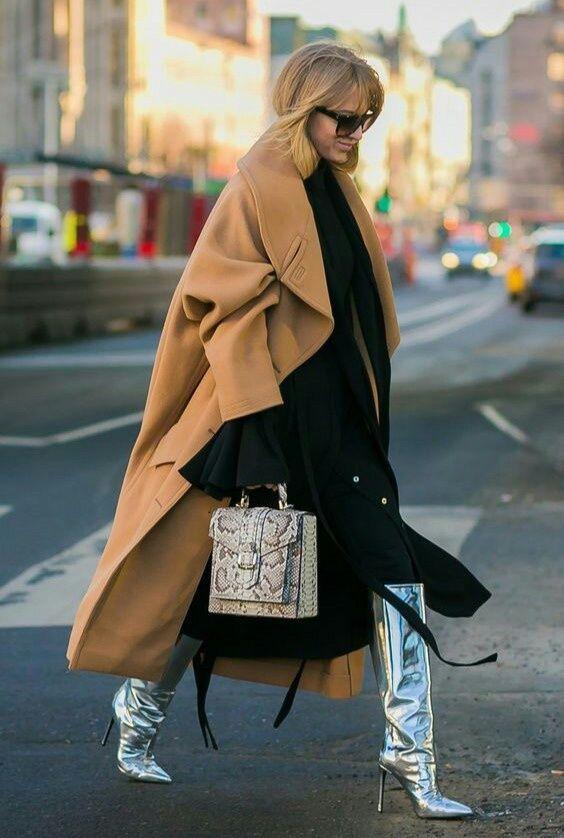 На девушке свободное черное платье-миди, бежевое замшевое пальто свободного кроя, сумка с анималистическим принтом, высокие сапоги на шпильке цвета металлик и очки.
