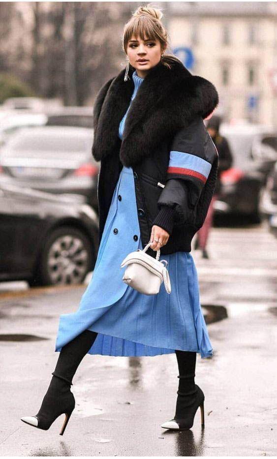 На девушке небесно-голубое платье-миди, свободная черная куртка с синими и красными полосами, мехом, черные сапоги- носки на шпильке с белым носом и белая маленькая сумка.