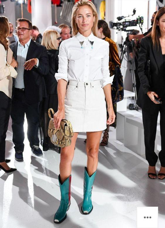 На девушке белая рубашка с металлическим воротником, джинсовая прямая короткая юбка, ковбойские высокие голубые сапоги на невысоком каблуке с квадратным носом и сумка анималистического принта.