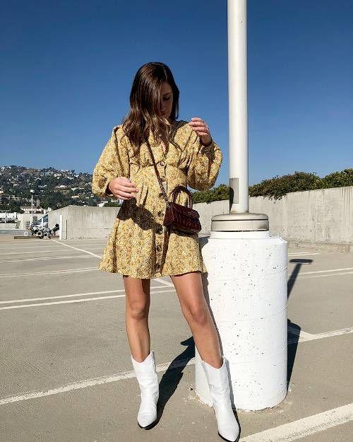 Цветочное желтое платье мини с пышными рукавами и пуговицами сочетается с белыми кожаными ковбойскими сапогами.