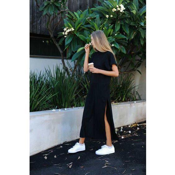 На девушке черное платье-футболка длины макси с коротким рукавом и разрезом и белые слипоны.