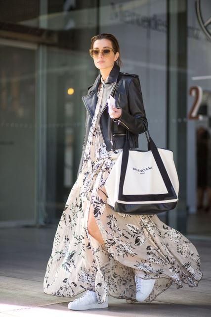 На девушке цветастое свободное шифоновое  платье миди в бежевых оттенках, кожаная черная куртка и белые слипоны. Образ дополнен объемной белой сумкой и очками.`