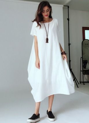 Белое однотонное объемное платье в сочетании с кожаными черными слипонами.