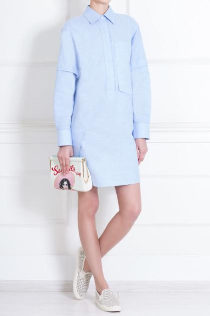Светло-голубая рубашка прямого кроя с длинным рукавом выше колена в сочетании с черно-белыми слипонами из ткани и белым клатчем с рисунком.