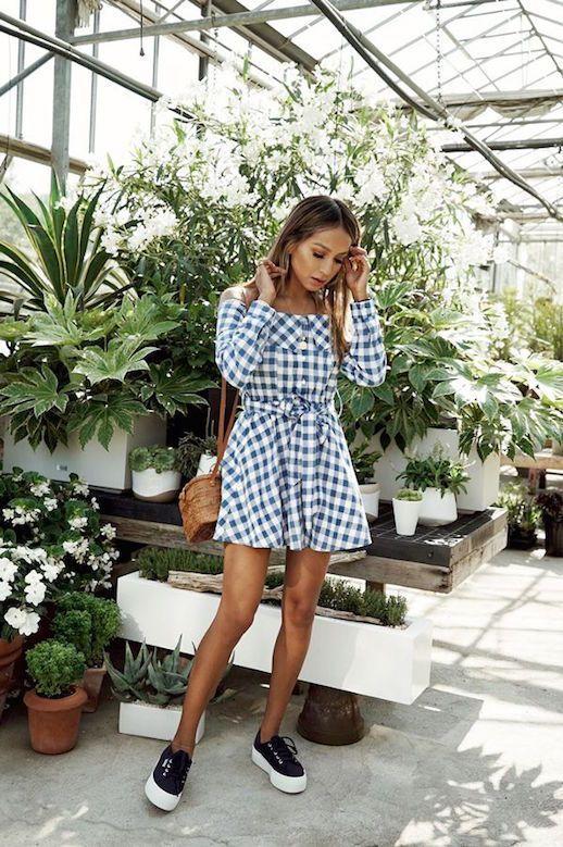 На девушке бело-голубое клетчатое платье-рубашка с поясом длины мини, веревочная поясная сумка и черные кожаные слипоны на высокой подошве.