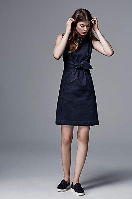Черное платье-рубашка прямого кроя с бантом отлично сочетается с черными слипонами.