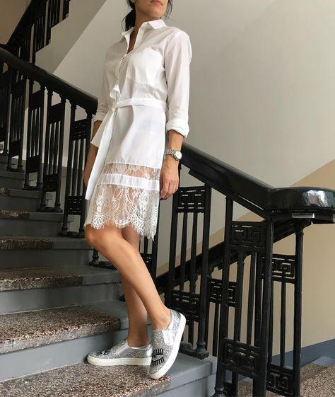 Белое платье-рубашка выше колена с поясом и кружевной вставкой сочетается с белыми слипонами, которые декорированы блестками и рисунком.