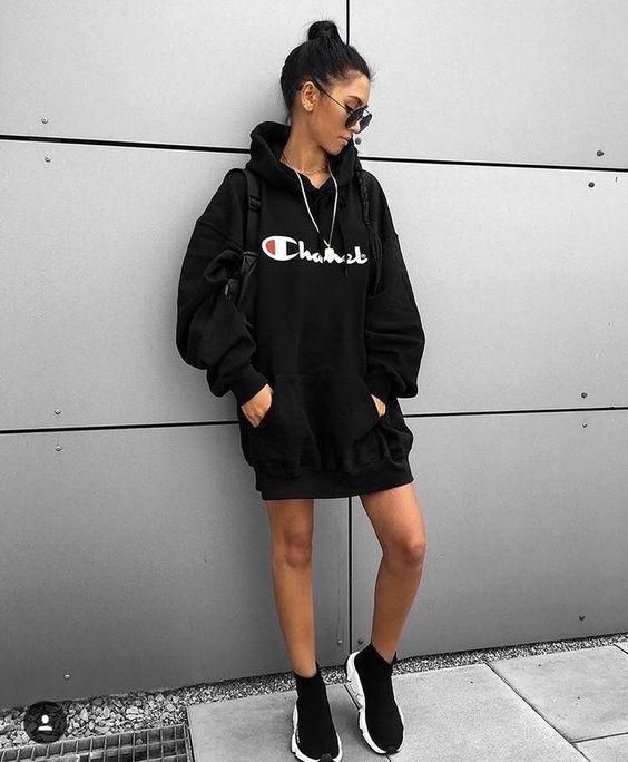 На девушке черное объемное платье-свитшот, черные слипоны, рюкзак и очки.