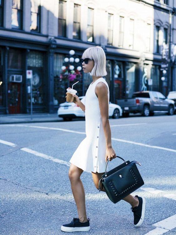 Белое платье свободного кроя с заклепками в сочетании с черными кожаными слипонами на белой подошве. Образ дополнен черной кожаной сумкой и очками.