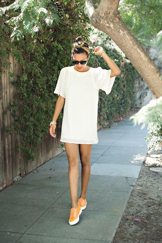 Белое платье-футболка свободного кроя в сочетании с ярко-оранжевыми слипонами. Образ дополнен банданой и очками.