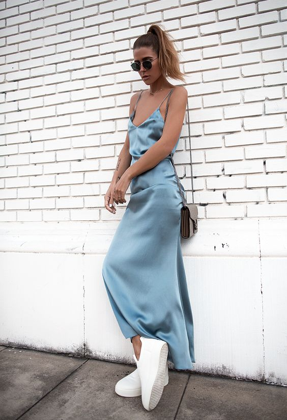 Шелковое платье макси на бретелях насыщенного голубого цвета в сочетании с белыми слипонами. Образ дополнен круглыми черными очками и поясной сумкой.