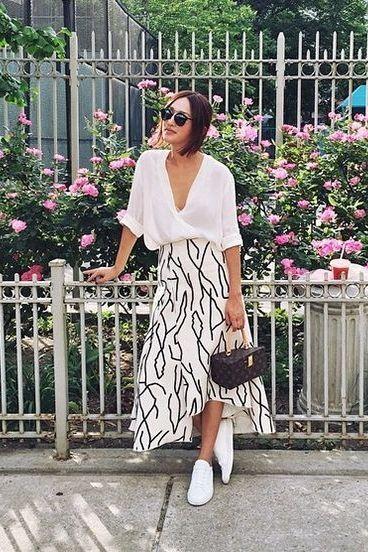 На девушке белая юбка макси с черными полосками, белые слипоны, очки и коричневая сумка.