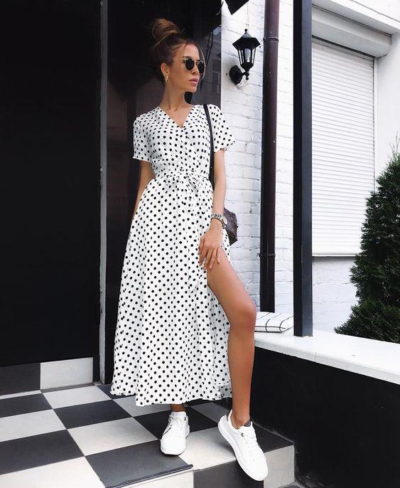 Белое платье с разрезом в черный горошек в сочетании с белыми слипонами. Образ дополнен черной поясной сумкой и очками.