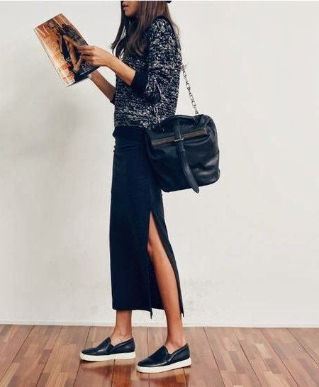 На девушке черное трикотажное платье свободного кроя с разрезом,объемный серый свитер, черная большая поясная сумка и кожаные слипоны.