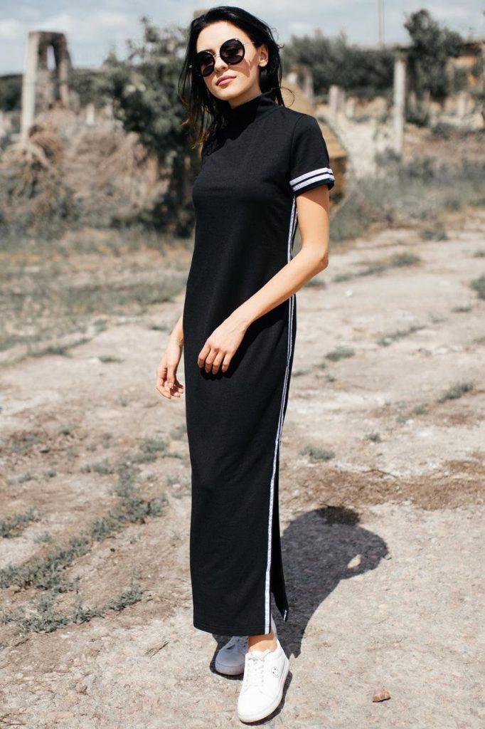 На девушке черное платье прямого кроя в пол с белыми полосами по бокам, белые слипоны и очки.