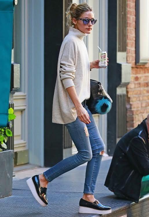 На девушке свободный бежевый свитер с высоким горлом, синие джинсы скинни и черные туфли на сплошной широкой белой платформе.